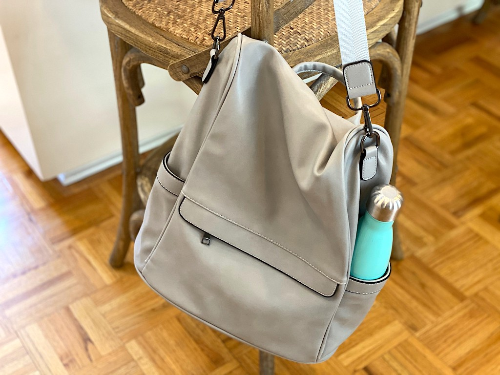 grey purse with water bottle handing from stool