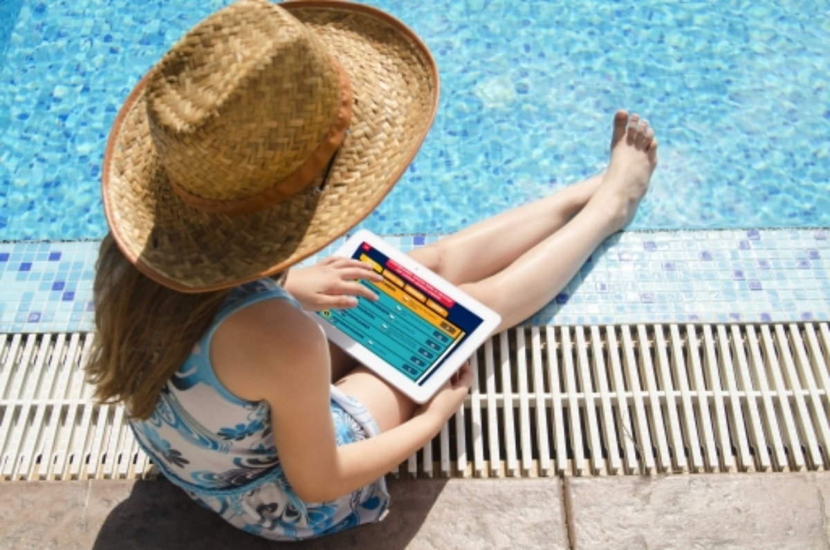 girl reading on tablet by pool