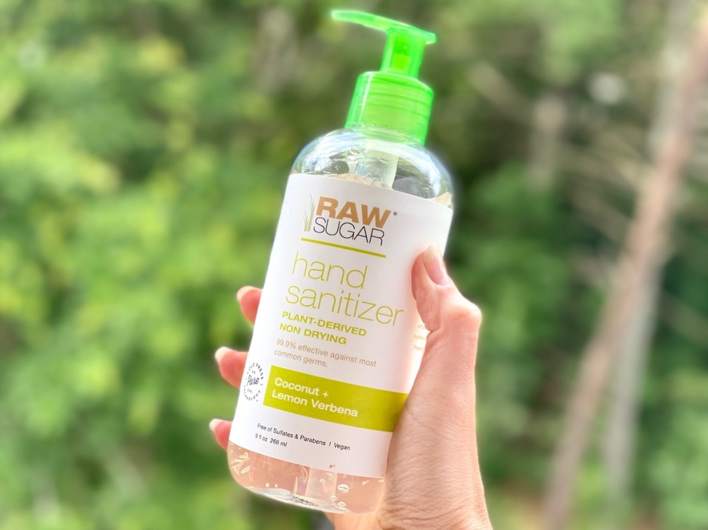 hand holding bottle of raw sugar hand sanitizer with trees in background