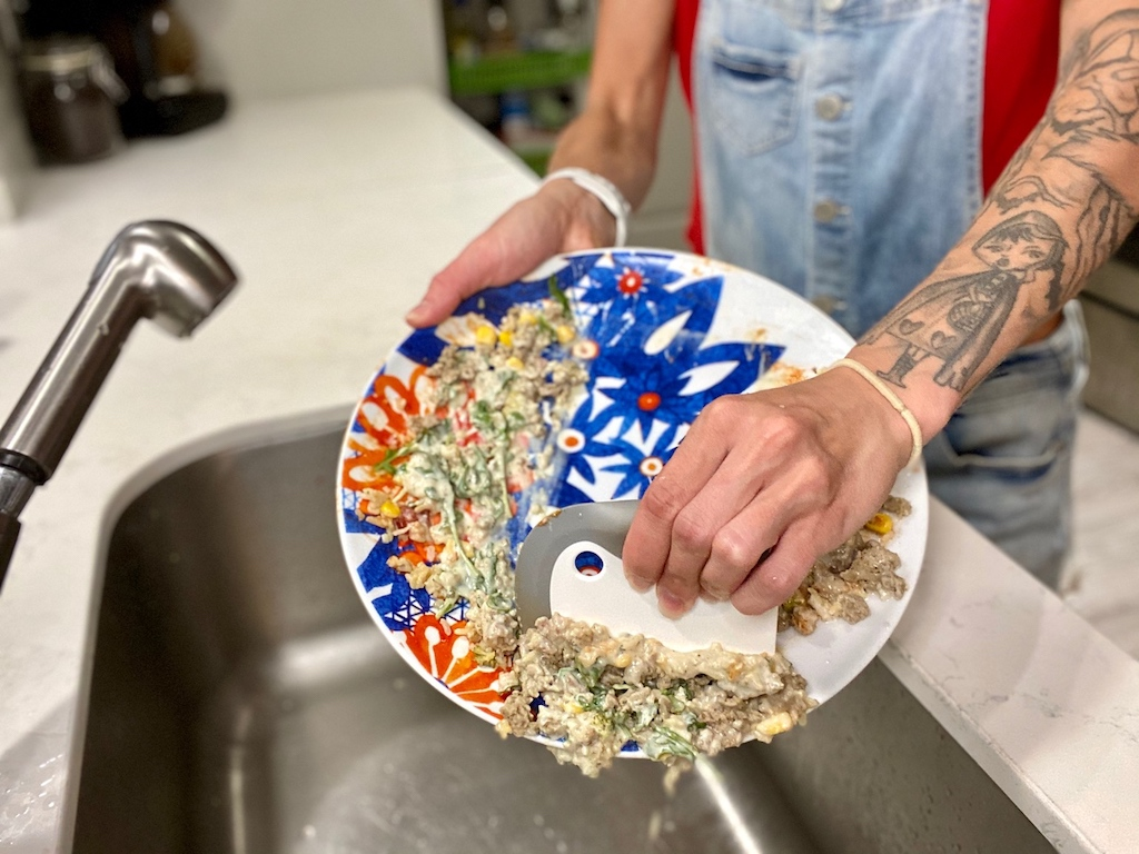 woman removing leftovers from plate with dish squeegee