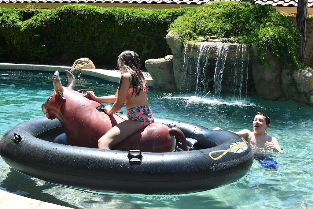 kids in pool with girl riding giant bull pool float