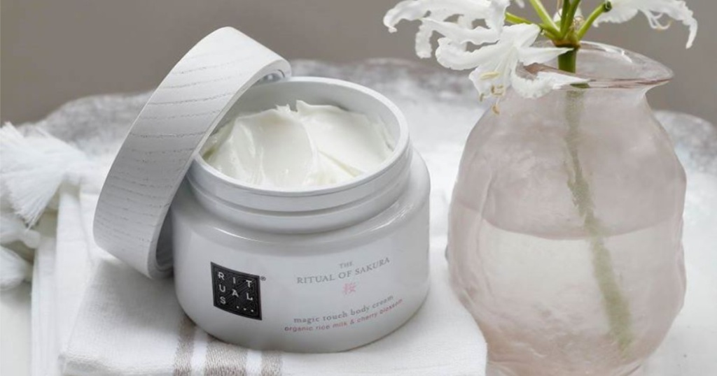 Rituals body cream with top part of the way off next to vase with flowers