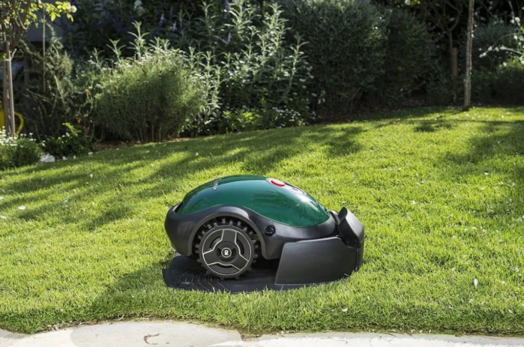 green robot lawn mower cutting green grass outside