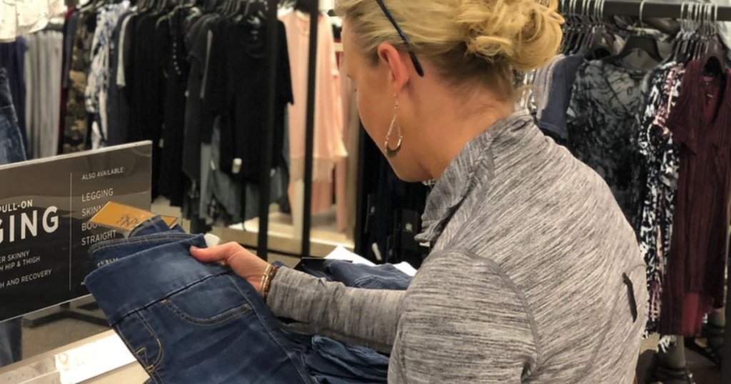 woman looking at jeans in store