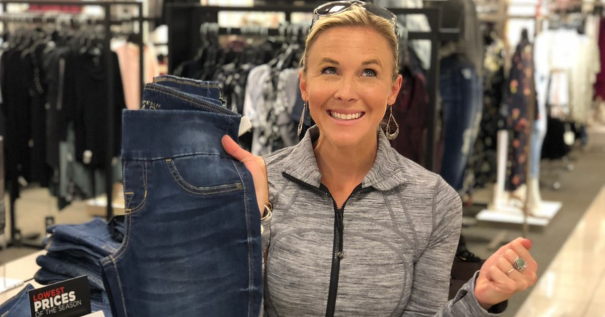woman holding up jeans in store and smiling