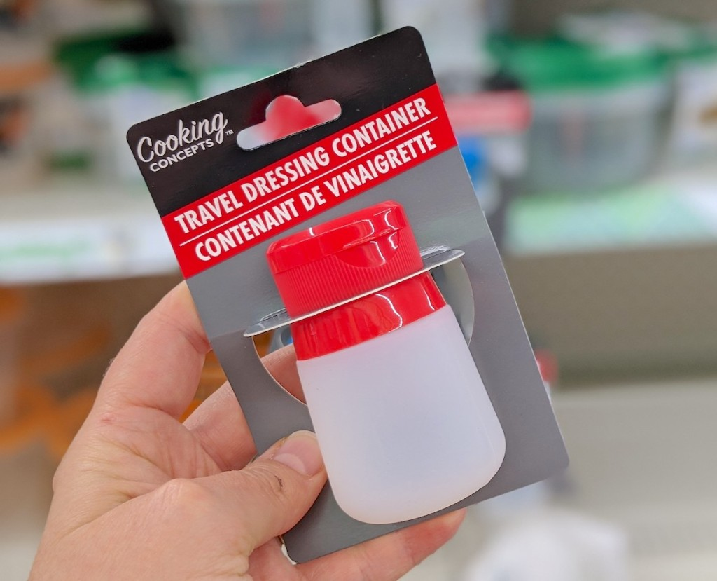 hand holding a clear and red silicone dressing bottle