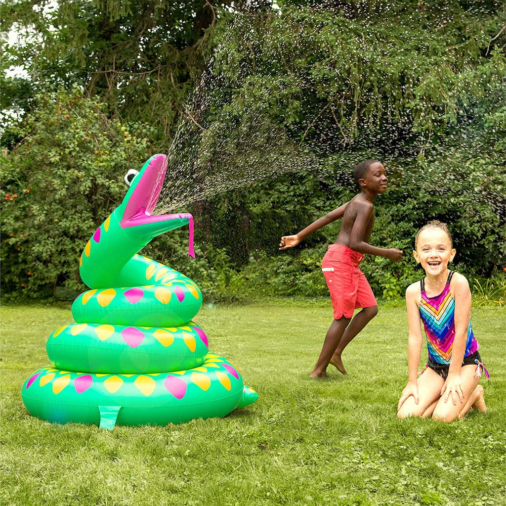 snake sprinkler spraying a boy and girl playing in the grass