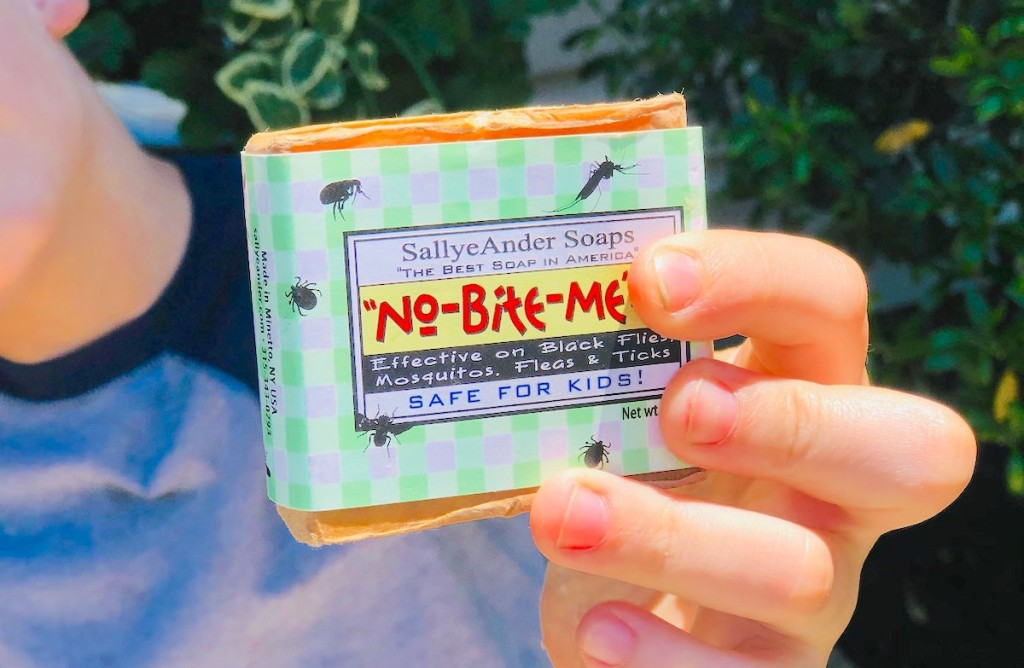 kid hand holding a bar of no bite me bug soap
