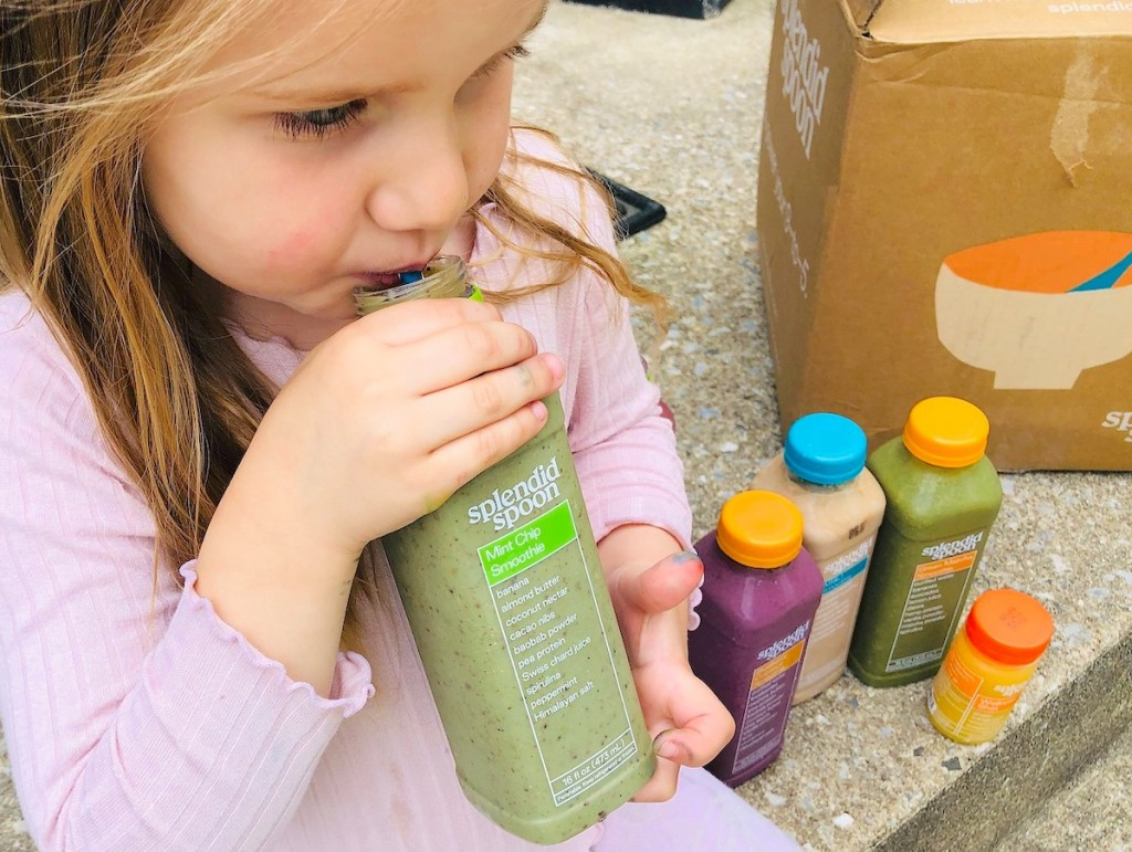 girl holding a green splendid spoon smoothie