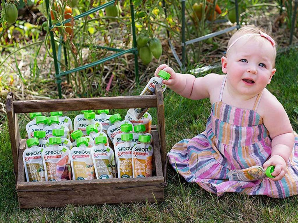 baby girls in grass next to container with baby food pouches