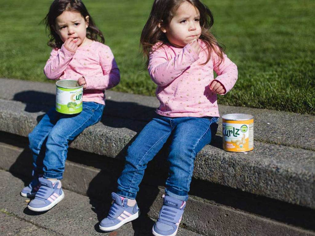 twin girls sitting on a ledge eating snacks