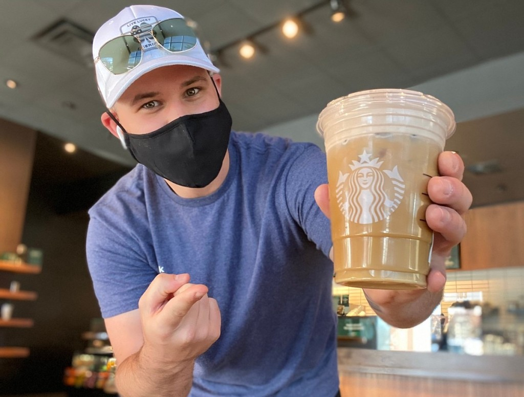 man holding a starbucks drink wearing a black mask on face