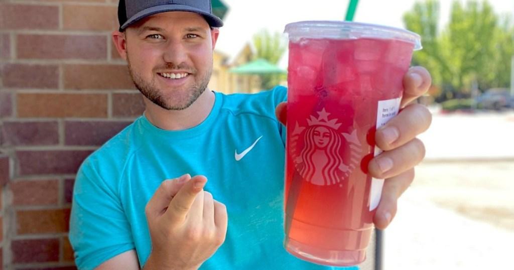 man holding pink Starbucks drink