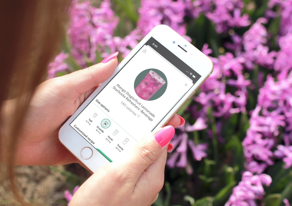 hand holding phone in front of purple flowers with starbucks refresher drink order on screen