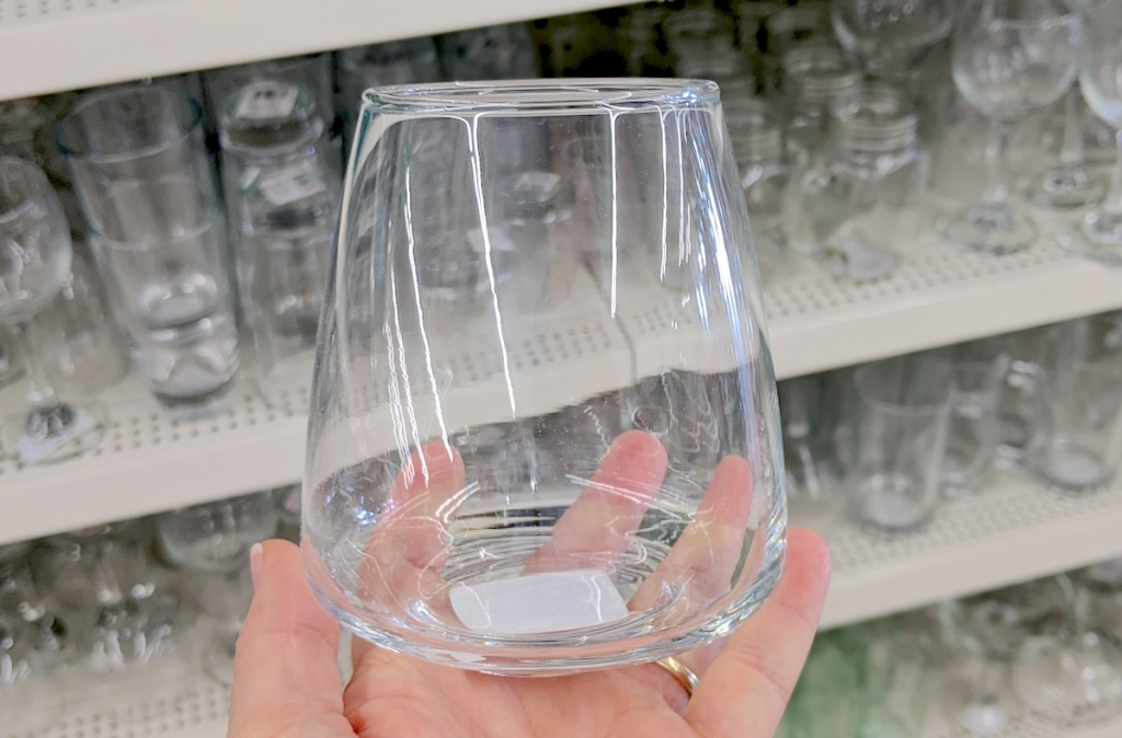 hand holding a clear stemless wine glass in store dish aisle