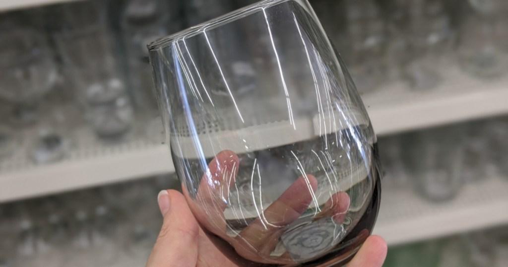hand holding stemless wine glass