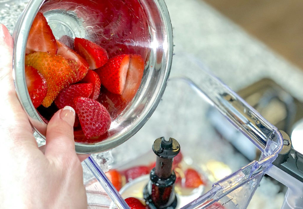 hand holding a stainless steel bowl of fresh strawberries dumping into blender