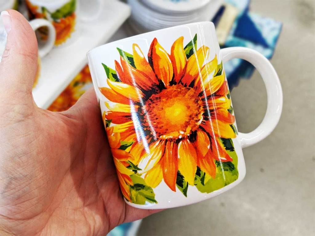 hand holding a sunflower mug up in a store