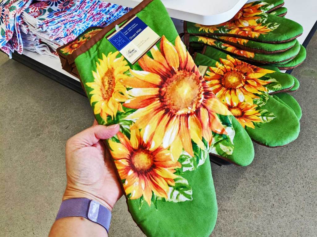 hand holding a sunflower oven mitt up in a store