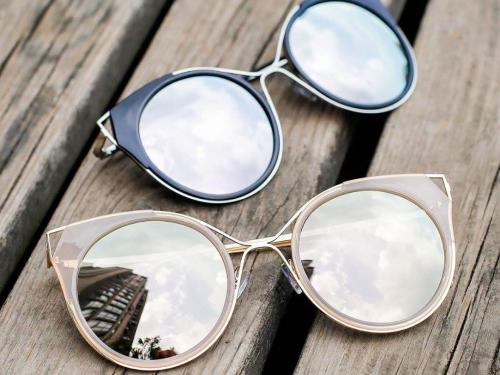 2 pairs of sunglasses on wood surface