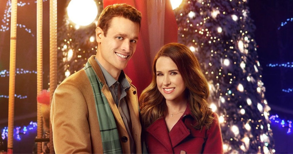 man and woman smiling in front of Christmas tree