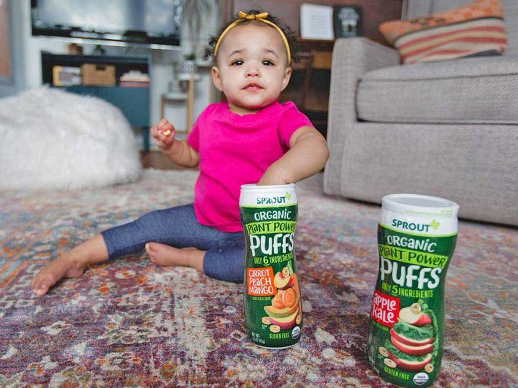toddler girl sitting on floor eating snacks