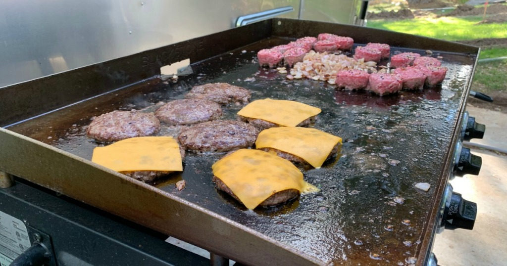 grilling burgers and onions on Blackstone griddle