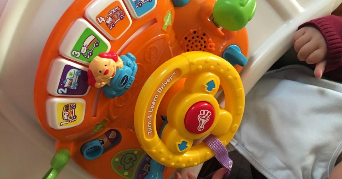 small child sitting by toy with steering wheel