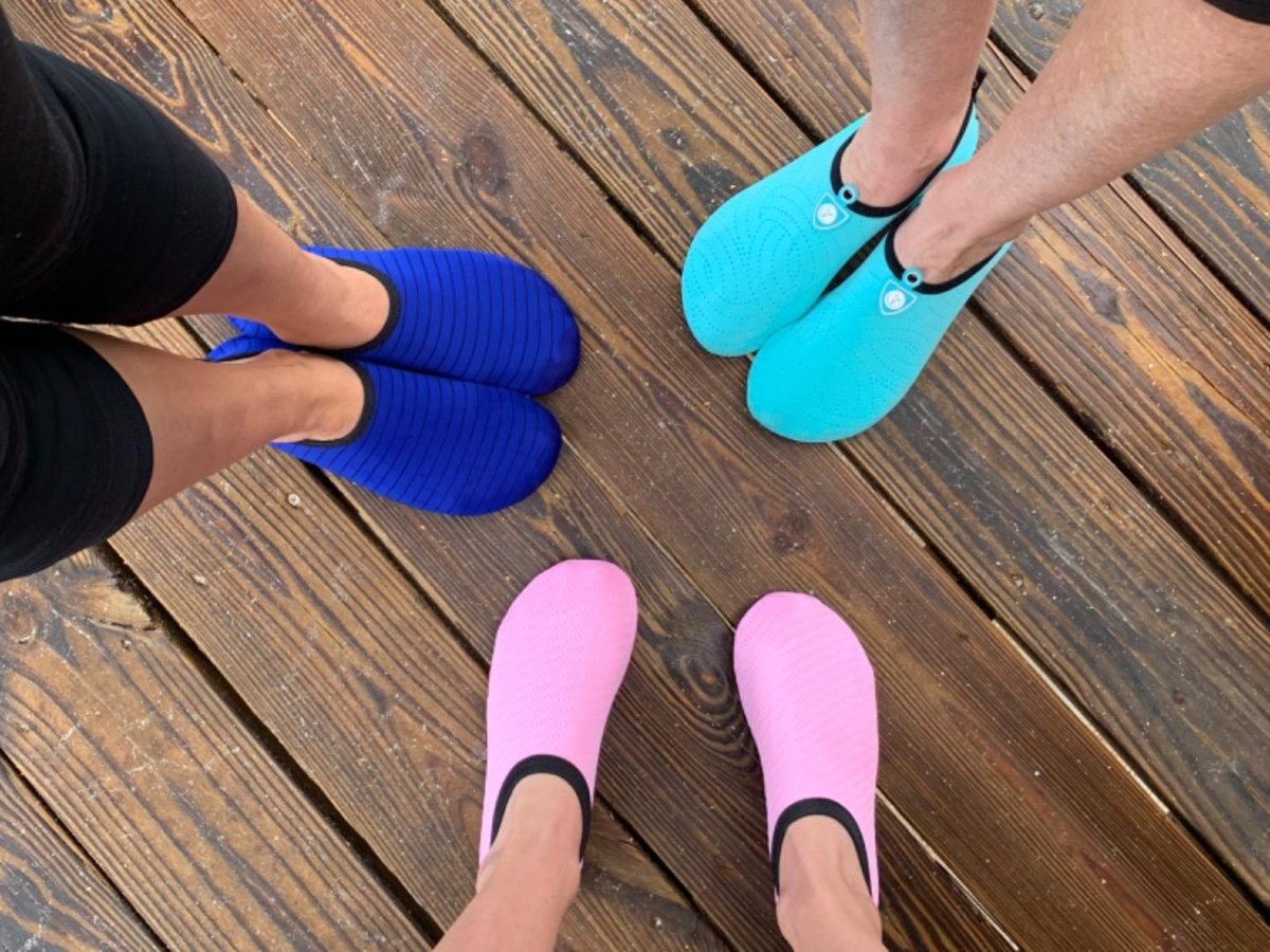 3 pairs of feet wearing different colored water shoes