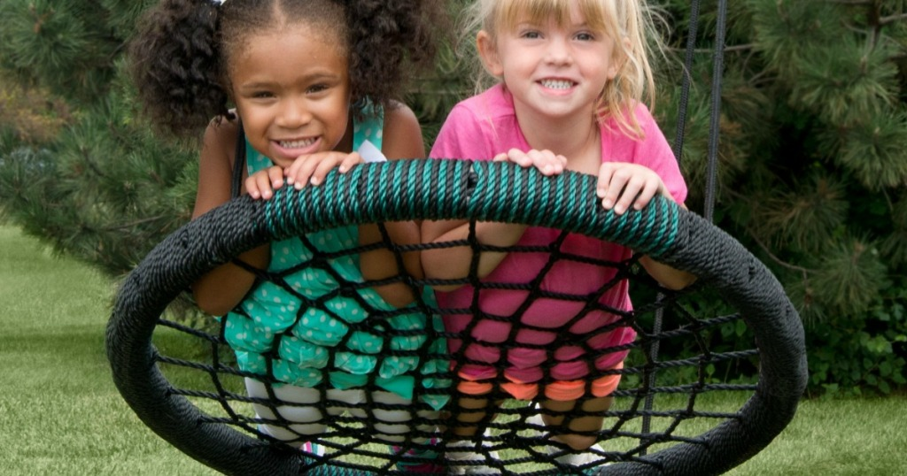 two kids on round webbed swing