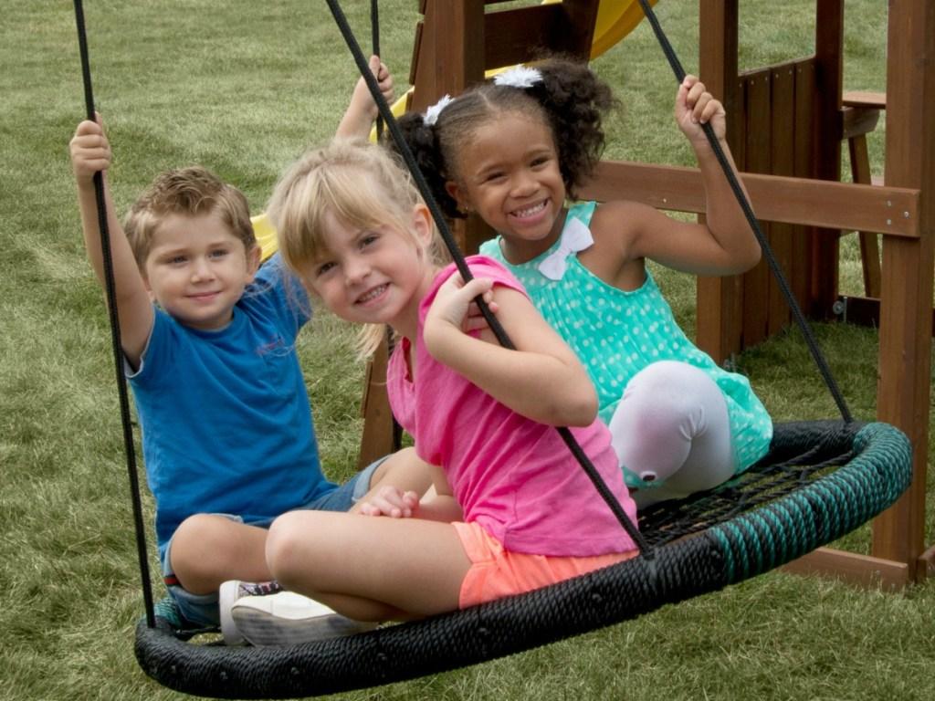 three kids sitting on round swing