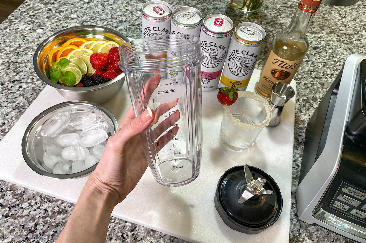 hand holding clear blender cup with various ingredients in background