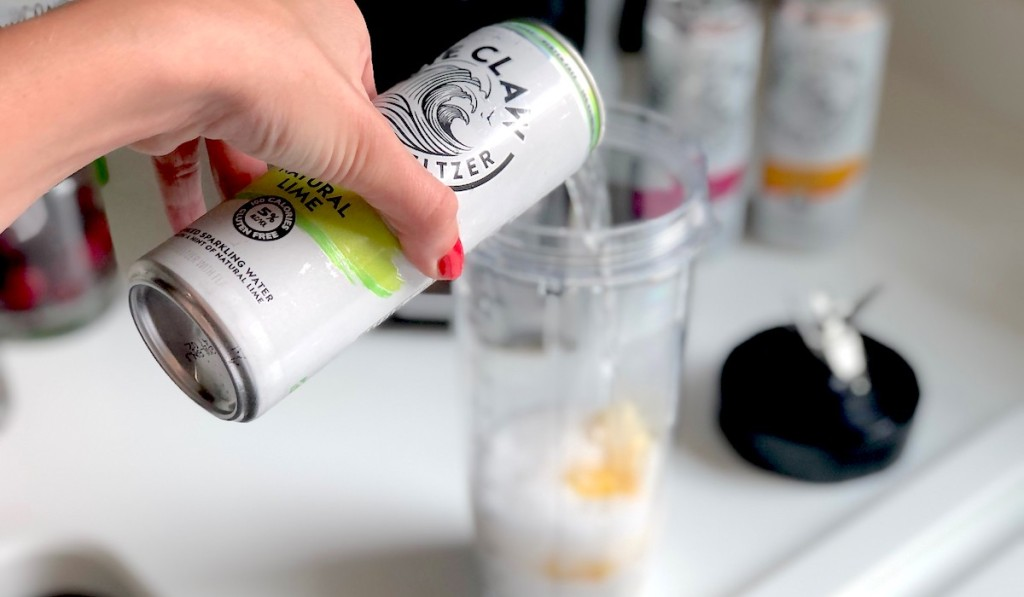 hand holding white claw can pouring into blending cup