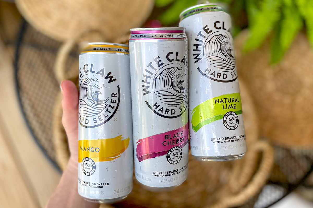 hand holding 3 kinds of white claw cans