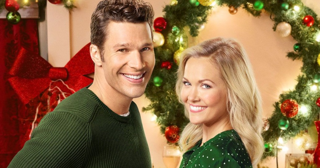 man and woman smiling in front of christmas wreath
