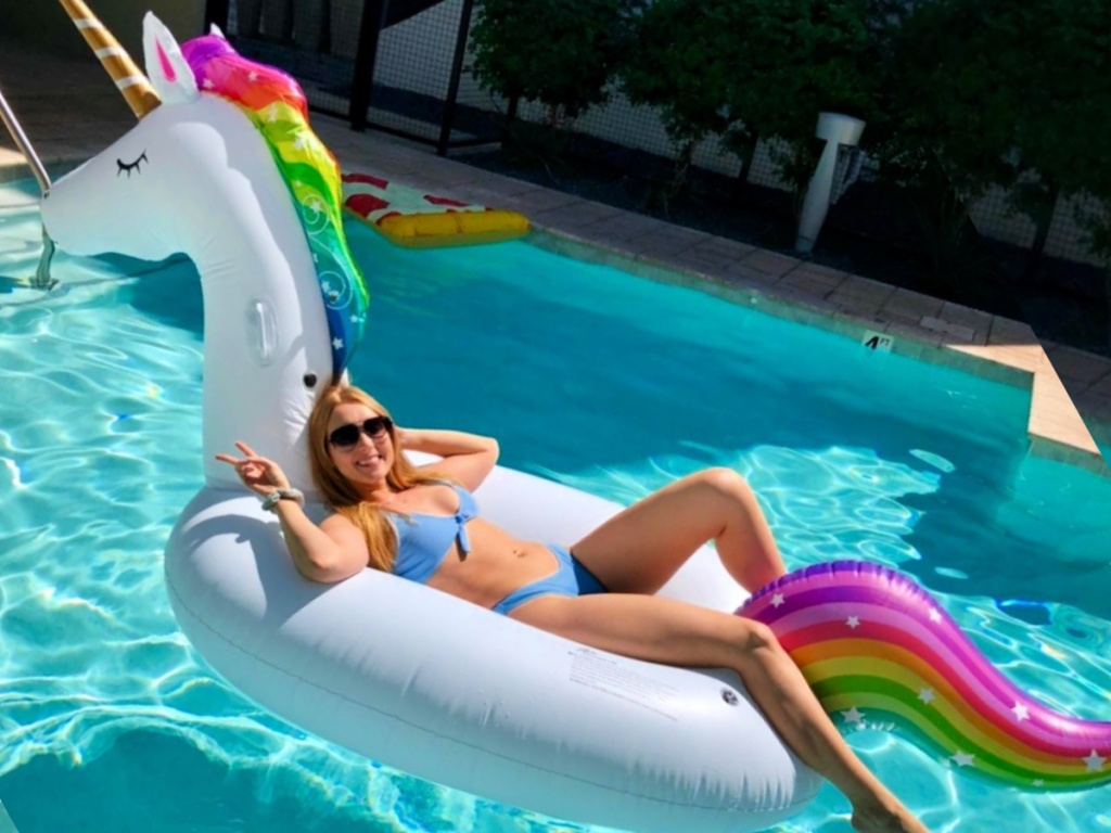 woman lounging on a Jasonwell Giant Inflatable Unicorn Pool Float Ride-On