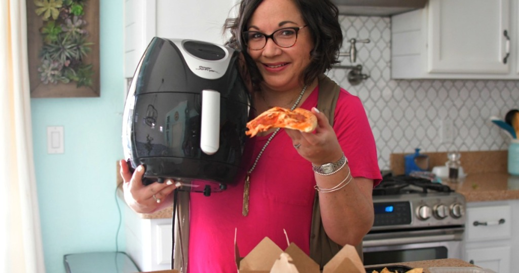 woman reheating pizza in air fryer