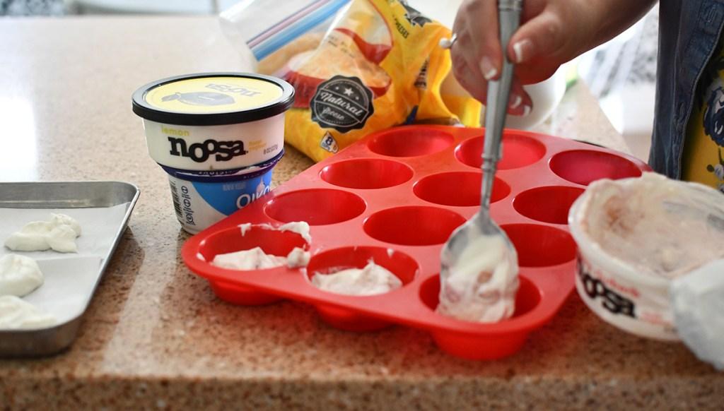 spooning yogurt into muffin tin