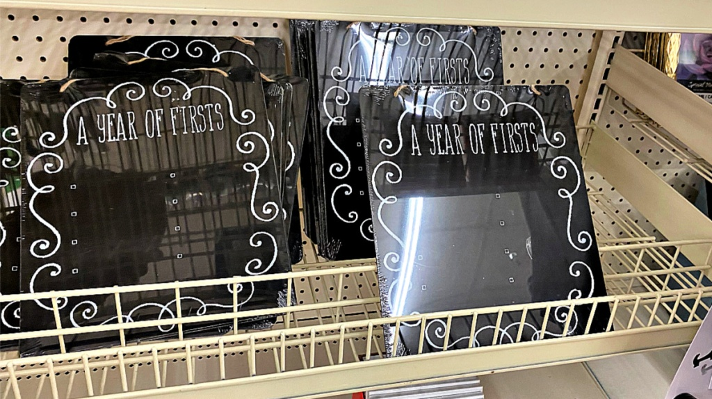 A Year of Firsts chalkboard signs on shelf at Dollar Tree