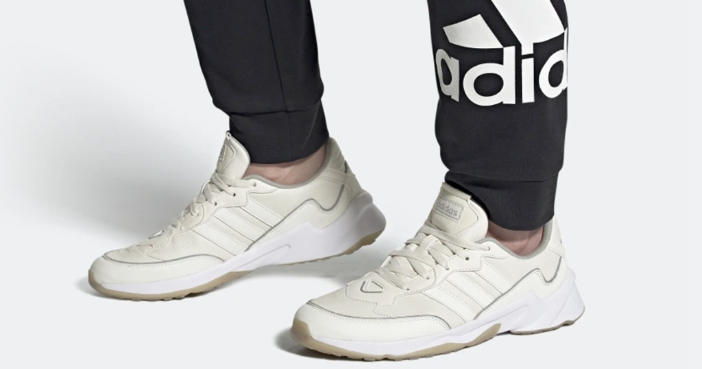 person in black adidas sweatpants wearing white and cream colored adidas sneakers