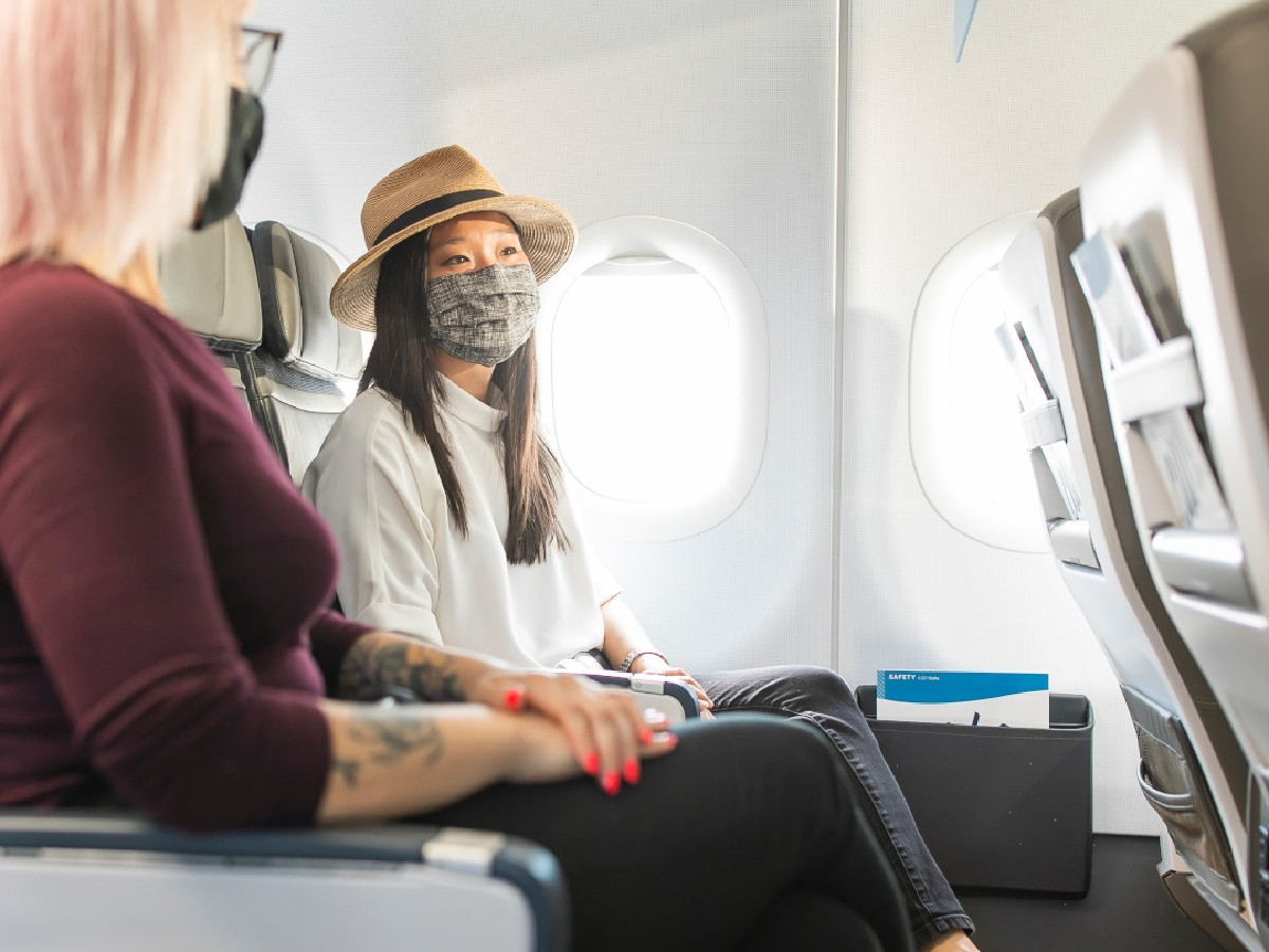 two women wearing face masks on airplane