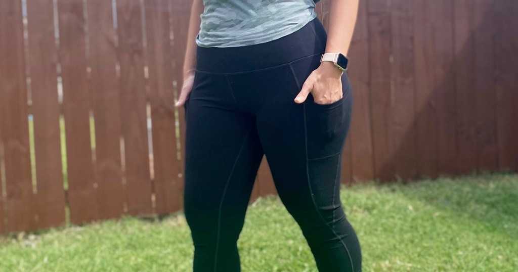 women standing in grassy yard wearing black leggings with her hands in pockets