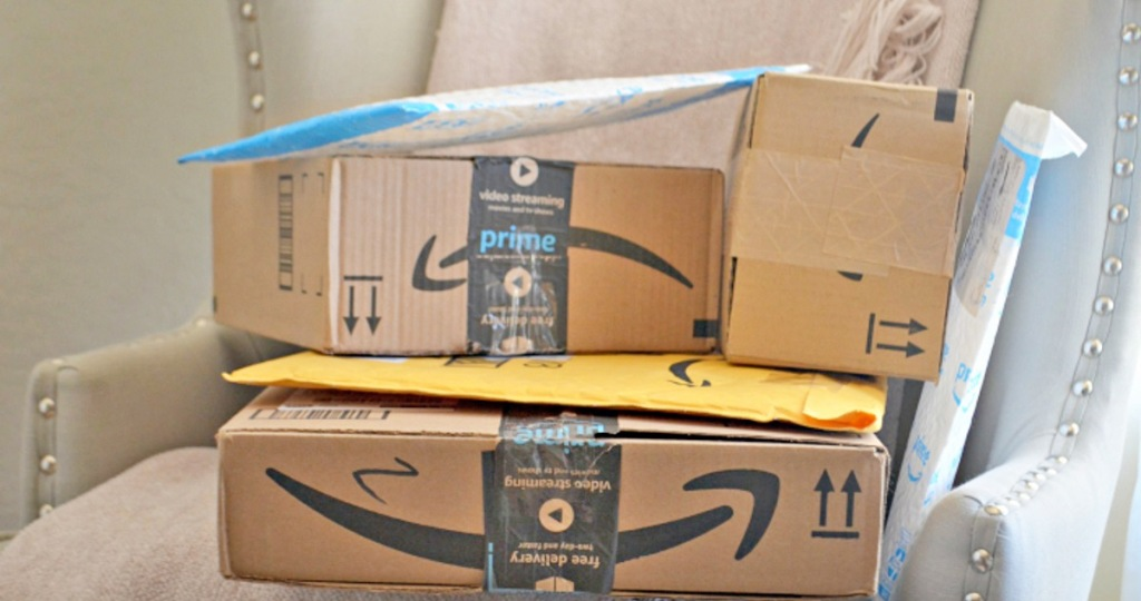 amazon boxes and packages stacked on an accent chair