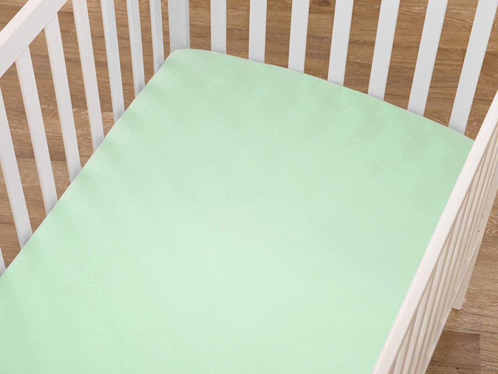 white crib with mint green sheets on mattress