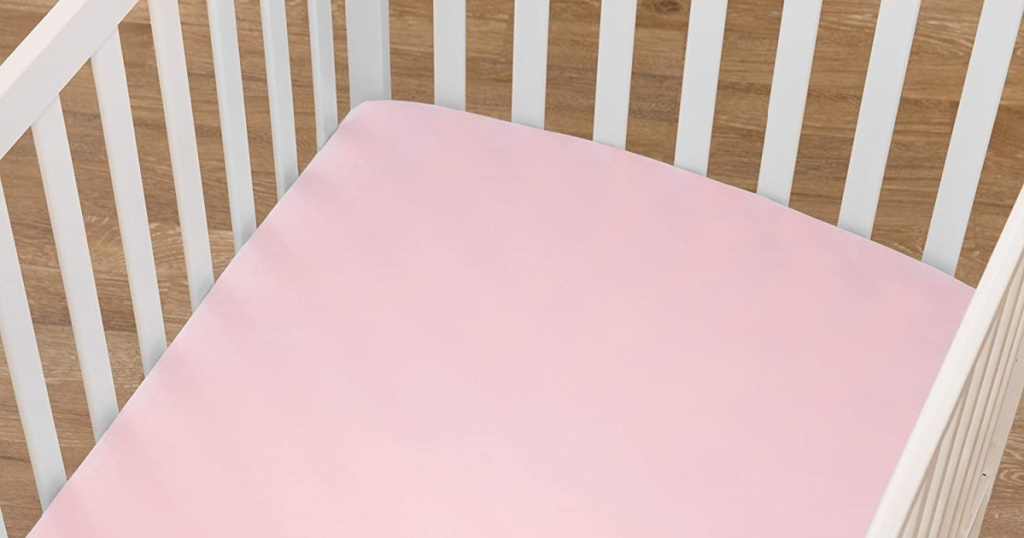 white crib with pink sheets on mattress