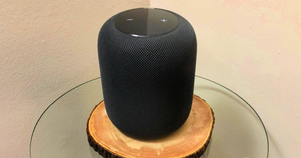 apple homepod sitting on a wooden disk on a small glass table