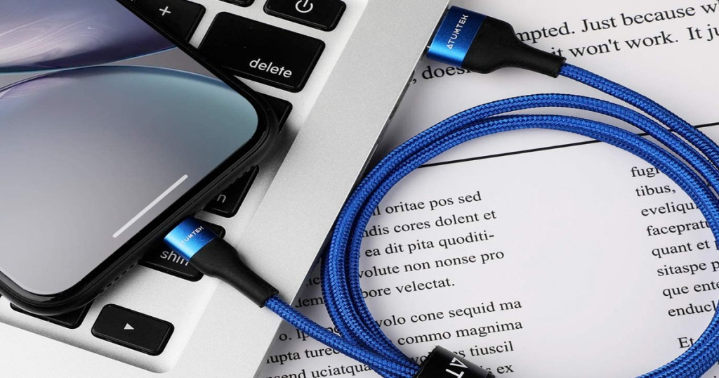 blue iphone charging cable coiled up and plugged into black iphone and silver macbook