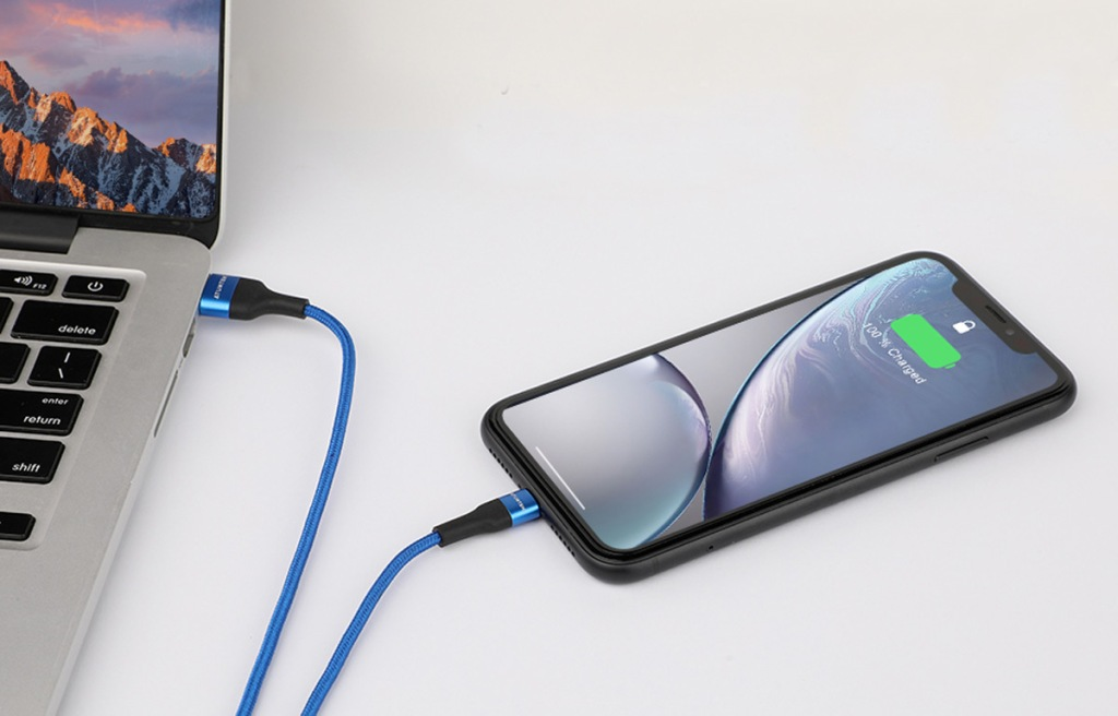 black iphone with blue charging cable plugged into macbook