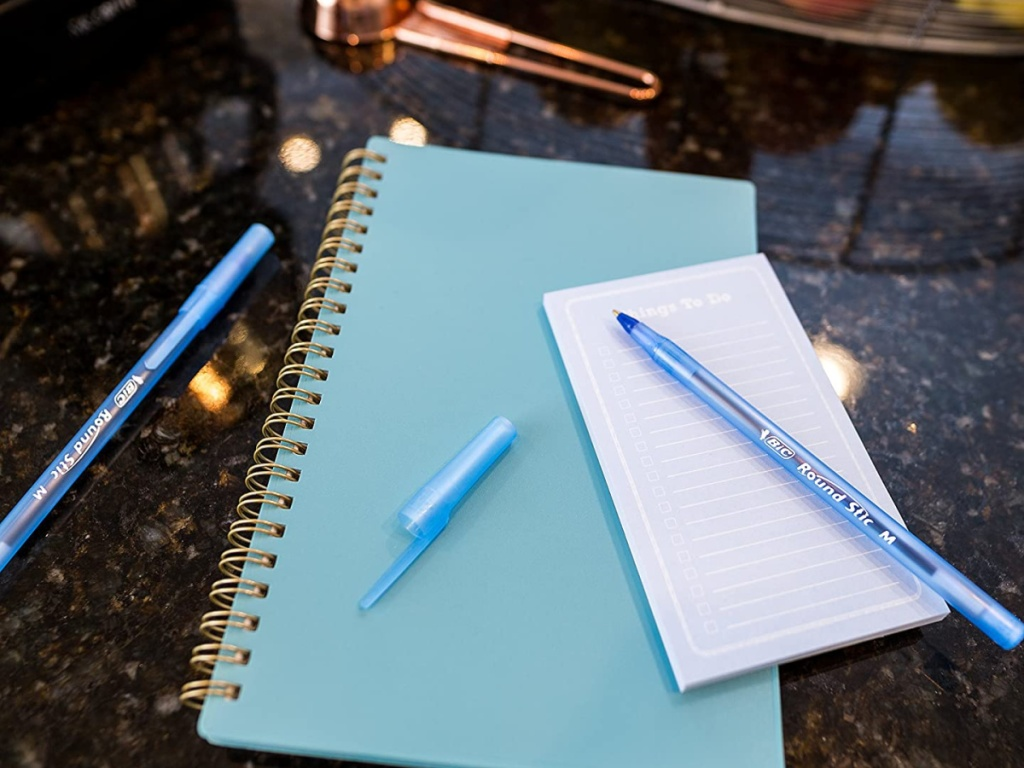 blue pens and blue notebook on marble counter