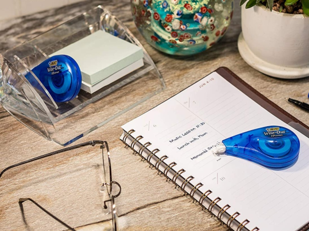 blue wite-out tape on desk with notebook, glasses, and more